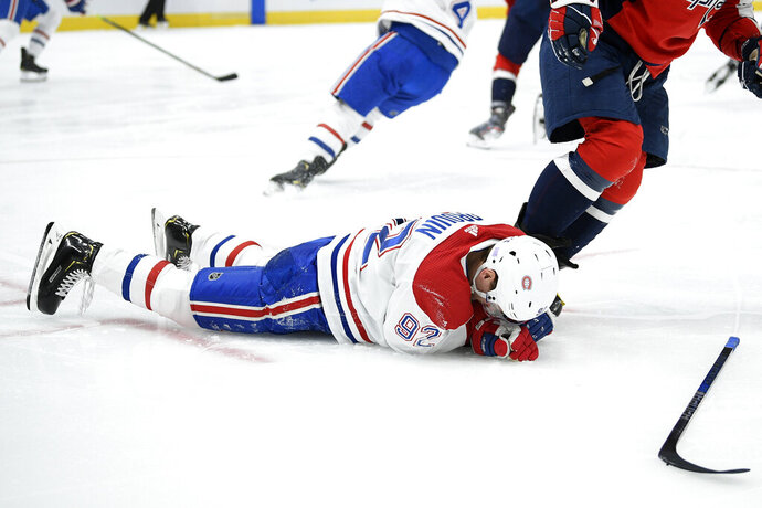 Montreal Canadiens left wing Jonathan Drouin (92) lies on the ice after a hit by Washington Capitals left wing Alex Ovechkin during the second period of an NHL hockey game, Friday, Nov. 15, 2019, in Washington. (AP Photo/Nick Wass)