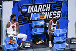 Arkansas' Vance Jackson (2) and Davonte Davis (4) watch from the bench area during the first half of a first round game against Colgate at Bankers Life Fieldhouse in the NCAA men's college basketball tournament, Friday, March 19, 2021, in Indianapolis. (AP Photo/Darron Cummings)