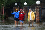 Isabelle Schneidau, left, gestures to the camera as she walks in a rising storm surge with Mont Echols, center, and L.G. Sullivan, right, after checking on their boats in the West End section of New Orleans in advance of Tropical Storm Cristobal in New Orleans, Sunday, June 7, 2020. (AP Photo/Gerald Herbert)