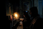 Iraq-born Archbishop Datev Hagopian, center, reads prayers during a Maundy Thursday religious service, that included the symbolic washing of feet for a few children, at the Armenian Church in Bucharest, Romania, Thursday, April 29, 2021. (AP Photo/Vadim Ghirda)