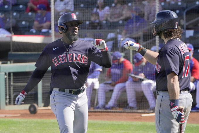 Cleveland Indians' Daniel Johnson, left, gets a fist bump from teammate Austin Hedges (17) after his a spring training baseball game Tuesday, March 9, 2021, in Surprise, Ariz. (AP Photo/Sue Ogrocki)