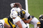 Northwestern running back Jesse Brown (1) scores on a 2-yard touchdown run over Iowa linebacker Nick Niemann during the second half of an NCAA college football game, Saturday, Oct. 31, 2020, in Iowa City, Iowa. (AP Photo/Charlie Neibergall)