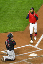 Minnesota Twins Byron Buxton, right, crosses home plate as Cleveland Indians catcher Roberto Perezlooks on after Buxton hit a two-run home run during the second inning of a game Friday, Sept. 11, 2020, in Minneapolis. (AP Photo/Craig Lassig)