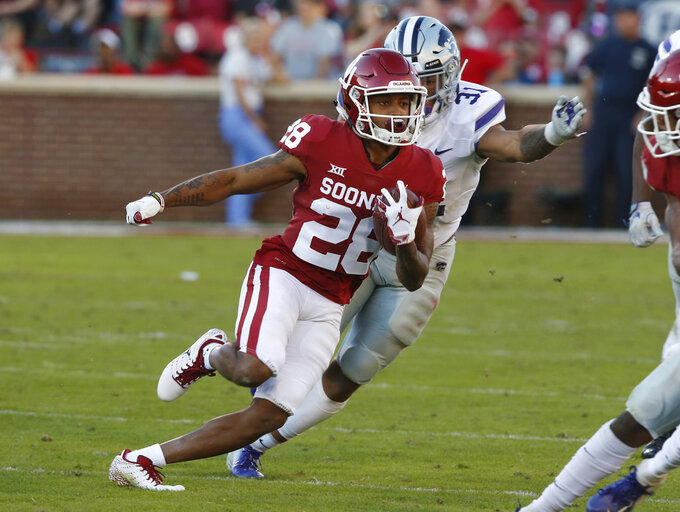 Oklahoma wide receiver Reggie Turner (28) carries past Kansas State defensive back Jahron McPherson (31) in the second half of an NCAA college football game in Norman, Okla., Saturday, Oct. 27, 2018. (AP Photo/Sue Ogrocki)
