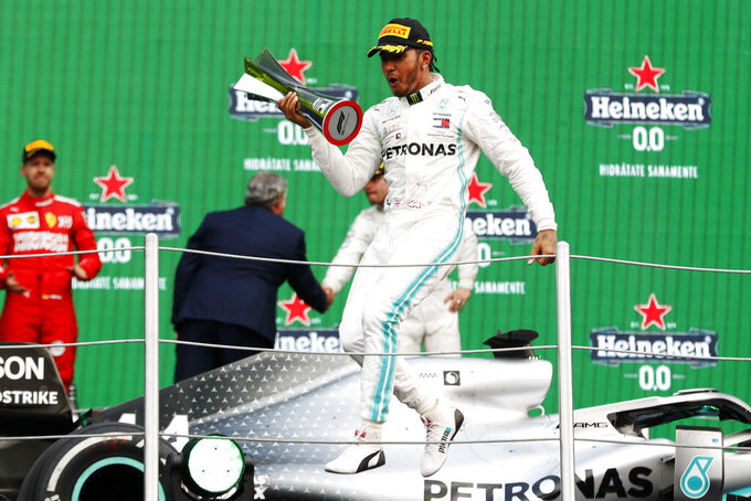 Mercedes driver Lewis Hamilton, of Britain, celebrates on the podium after winning the Formula One Mexico Grand Prix auto race at the Hermanos Rodriguez racetrack in Mexico City, Saturday, Oct. 26, 2019. (AP Photo/Eduardo Verdugo)