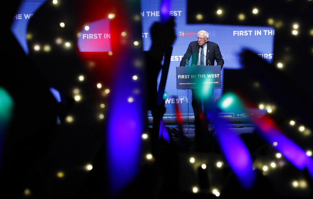 FILE - In this Sunday, Nov. 17, 2019 file photo, Democratic presidential candidate Sen. Bernie Sanders, I-Vt., speaks as supporters wave lighted signs during a fundraiser for the Nevada Democratic Party in Las Vegas. During the 2020 campaign, Sanders, who's known more for eschewing organized religion than embracing his Jewishness, has shifted the way he talks about his faith and tied it to his broader worldview. (AP Photo/John Locher)