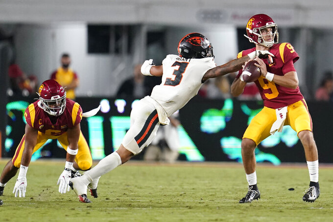 Southern California quarterback Kedon Slovis is pressured by Oregon State defensive back Jaydon Grant (3) during the first half of an NCAA college football game Saturday, Sept. 25, 2021, in Los Angeles. (AP Photo/Marcio Jose Sanchez)
