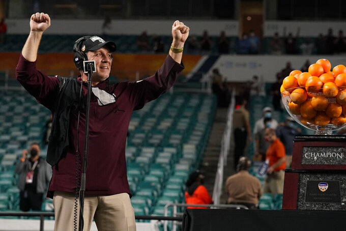 Texas A&M head coach Jumbo Fisher raises his hands during the trophy presentation at the Orange Bowl NCAA college football game, Saturday, Jan. 2, 2021, in Miami Gardens, Fla. Texas A&M defeated North Carolina 41-27. (AP Photo/Lynne Sladky)