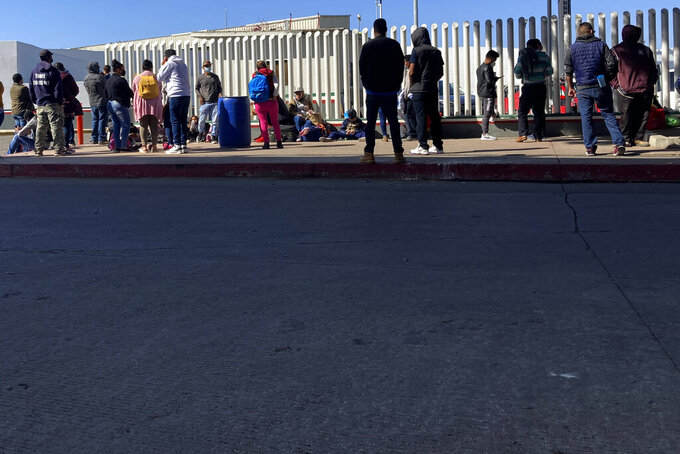 """FILE - Migrants waiting to cross into the United States wait for news at the border crossing Wednesday, Feb. 17, 2021, in Tijuana, Mexico.  A federal appellate court refused late Thursday, Aug. 19 to delay implementation of a judge's order reinstating a Trump administration policy forcing thousands to wait in Mexico while seeking asylum in the U.S. President Joe Biden had suspended former President Donald Trump's """"Remain in Mexico"""" policy on his first day in office and the Department of Homeland Security said it was permanently terminating the program in June, according to the court record.  (AP Photo/Elliot Spagat)"""