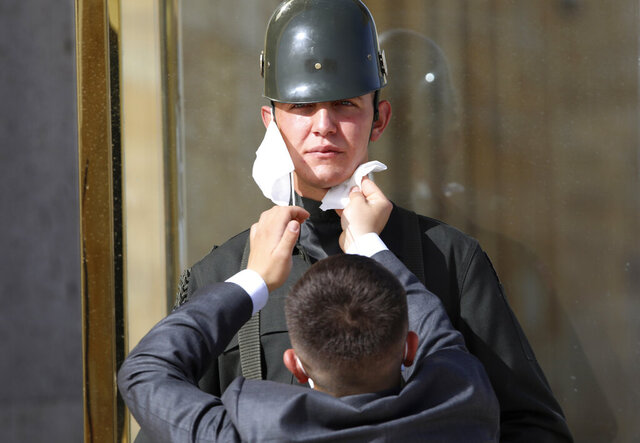 A man wipes the face of a Turkish soldier wearing a face mask for protection against the new coronavirus, before a ceremony at the mausoleum of Mustafa Kemal Ataturk, the founder of modern Turkey, in Ankara, Turkey, Tuesday, May 19, 2020. This year's limited ceremony is marking the 101st anniversary of the start of Turkey's War of Independence under the leadership of the young Ottoman army general. (AP Photo/Burhan Ozbilici)