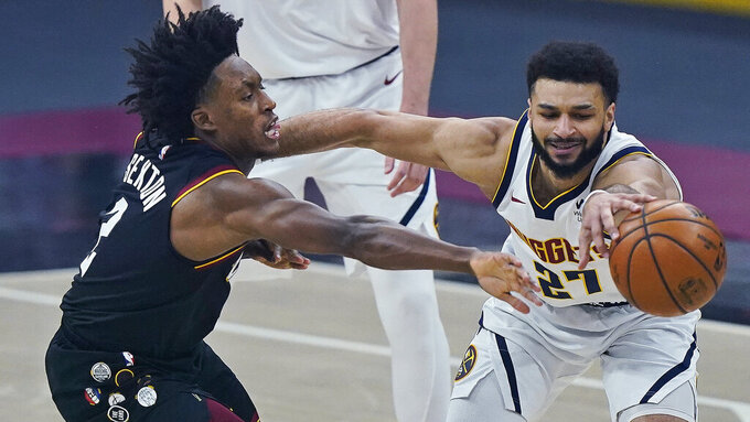Cleveland Cavaliers' Collin Sexton, left, and Denver Nuggets' Jamal Murray reach for the ball during the first half of an NBA basketball game Friday, Feb. 19, 2021, in Cleveland. (AP Photo/Tony Dejak)