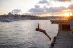 A youth jumps into the Golden Horn in Istanbul, Friday, Sept. 11, 2020. Turkey is getting tough on people who flout self-isolation rules despite testing positive for the coronavirus. An Interior Ministry circular sent to the country's 81 provinces on Friday said people caught leaving their homes despite isolation orders will be quarantined and supervised at state-owned dormitories or hostels.   (AP Photo/Yasin Akgul)