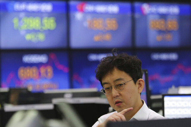 A currency trader watches monitors at the foreign exchange dealing room of the KEB Hana Bank headquarters in Seoul, South Korea, Tuesday, Feb. 11, 2020. Asian stock markets followed Wall Street higher on Tuesday, at least temporarily shaking off jitters about China's virus outbreak. (AP Photo/Ahn Young-joon)