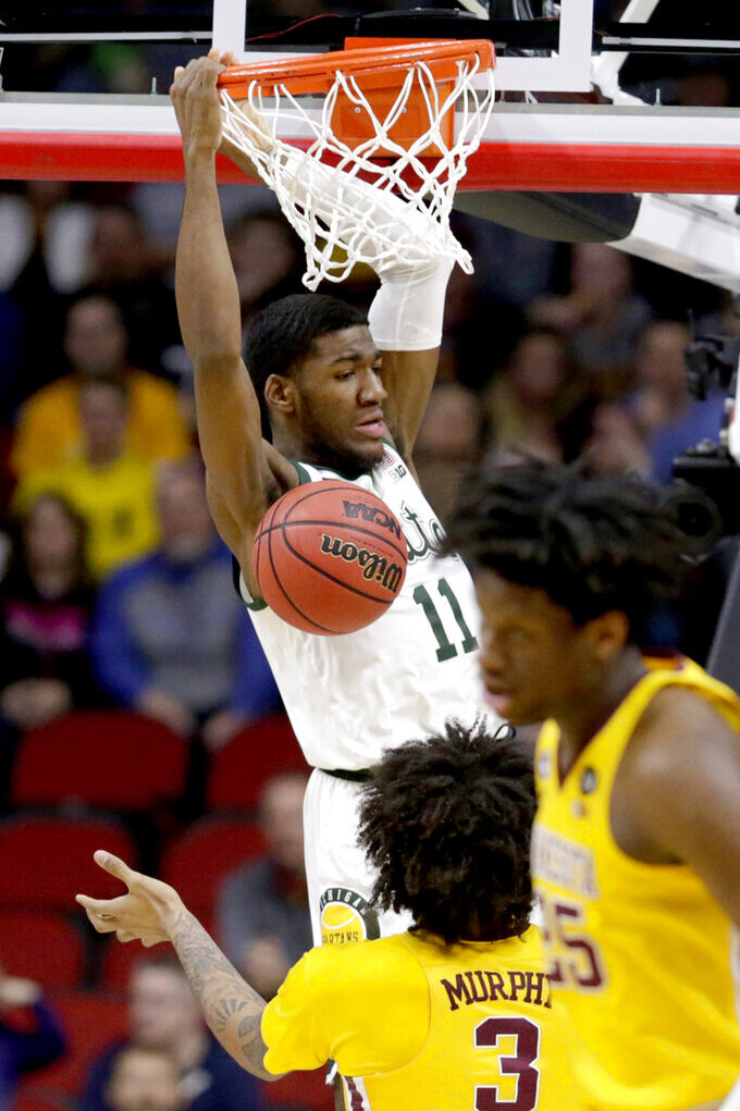 Michigan State's Aaron Henry (11) dunks as Minnesota's Jordan Murphy (3) and Matz Stockman (35) watch, during the first half of a second round men's college basketball game in the NCAA Tournament, in Des Moines, Iowa, Saturday, March 23, 2019. (AP Photo/Nati Harnik)