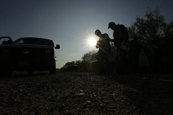 FILE - In this Nov. 6, 2019, file photo, Border Patrol agents stop men thought to have entered the country illegally, near McAllen, Texas, along the U.S.-Mexico border. President Joe Biden rushed to send the most ambitiousoverhaul of the nation's immigration system in a generationto Congress and signednine executive actionsto wipe out some of his predecessor's toughest measures to fortify the U.S.-Mexico border. But a federal court in Texas suspended his 100-day moratorium on deportations. (AP Photo/Eric Gay, File)