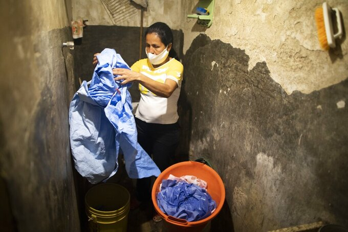 Elena Suazo hand washes the protective medical clothing she wears when she attends her father who is hospitalized with COVID-19, in the bathroom at her parent's home before hang drying them, in the Catia neighborhood of Caracas, Venezuela, Tuesday, Sept. 29, 2020. On a cafeteria worker's monthly salary of less than $ , Suazo had no money to buy the needed protective gear, so her younger brother bought her one suit and her son's mother-in-law gave her a second, allowing her to attend him inside the hospital twice a day. (AP Photo/Ariana Cubillos)