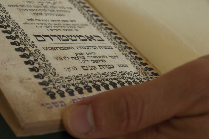 In this Monday, Nov. 11, 2019 photo, Israeli National Library official holds a text of Rabbi Isaac Abarbanel from the 15th century, published in Amsterdam in 1739, at the library in Jerusalem. The National Library of Israel says it will digitize 120,000 books for the first time as part of a historic collaboration with Google. The library said in a statement Monday that its contribution to Google Books will significantly increase the percentage of Hebrew texts available online. (AP Photo/Patty Nieberg)