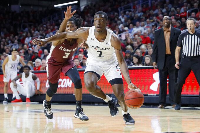 Cincinnati's Keith Williams (2) drives past Alabama A&M's Cameron Tucker (3) during the first half of an NCAA college basketball game Thursday, Nov. 14, 2019, in Cincinnati. (AP Photo/John Minchillo)