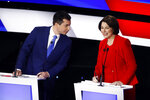 Democratic presidential candidates former South Bend Mayor Pete Buttigieg, left, and Sen. Amy Klobuchar, D-Minn., right, talk during a break Tuesday, Jan. 14, 2020, in a Democratic presidential primary debate hosted by CNN and the Des Moines Register in Des Moines, Iowa. (AP Photo/Patrick Semansky)