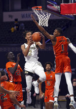 Wake Forest's Jalen Johnson sinks a lay up as he drives to the basket between Miami's Deng Gak (22) and Anthony Walker (1) during an NCAA college basketball game, Saturday, Jan. 30, 2021, at Joel Coliseum in Winston-Salem, N.C. (Walt Unks/The Winston-Salem Journal via AP)