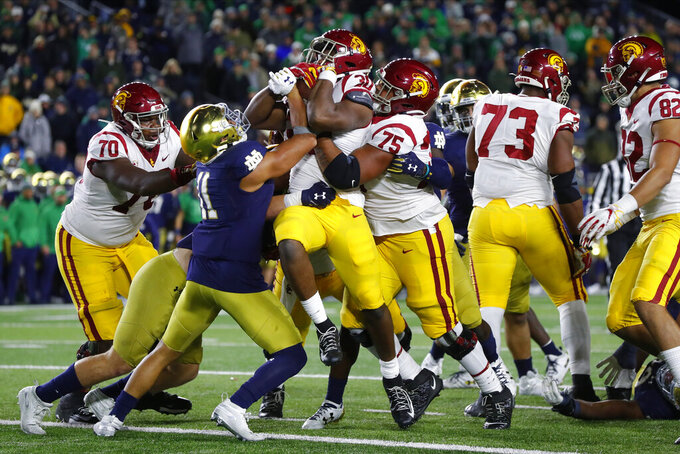 FILE - In this Oct. 12, 2019, file photo, Southern California running back Markese Stepp (30) is lifted into the end zone by Alijah Vera-Tucker (75) as Notre Dame safety Alohi Gilman defends in the second half of an NCAA college football game, in South Bend, Ind. Vera-Tucker was selected to The Associated Press All-Pac 12 Conference team, Thursday, Dec. 12, 2019. (AP Photo/Paul Sancya, File)