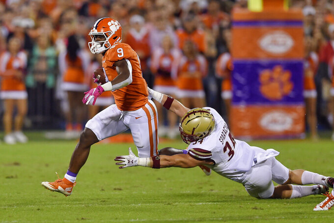 Clemson's Travis Etienne (9) rushes while defended by Boston College's Joseph Sparacio during the first half of an NCAA college football game Saturday, Oct. 26, 2019, in Clemson, S.C. (AP Photo/Richard Shiro)
