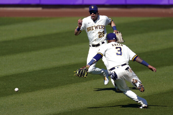 Milwaukee Brewers shortstop Orlando Arcia (3) and right fielder Christian Yelich (22) chase a ball hit by Chicago Cubs' Ian Happ, who reached first base on a fielding error, during the third inning of a spring training baseball game Saturday, March 6, 2021, in Phoenix. (AP Photo/Ashley Landis)