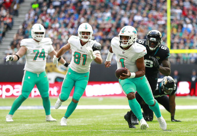 Miami Dolphins quarterback Tua Tagovailoa (1) runs with the ball during an NFL football game between the Miami Dolphins and the Jacksonville Jaguars at the Tottenham Hotspur stadium in London, England, Sunday, Oct. 17, 2021. (AP Photo/Ian Walton)