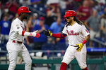 Philadelphia Phillies' Freddy Galvis, right, and Andrew McCutchen celebrate after Galvis' two-run home run against Chicago Cubs pitcher Alec Mills during the fourth inning of a baseball game, Wednesday, Sept. 15, 2021, in Philadelphia. (AP Photo/Matt Slocum)