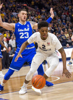 Marquette forward Sacar Anim, right, goes for the loose ball against the defense of Seton Hall forward Sandro Mamukelashvili, left, during the first half of an NCAA college basketball game Saturday, Jan. 12, 2019, in Milwaukee. (AP Photo/Darren Hauck)
