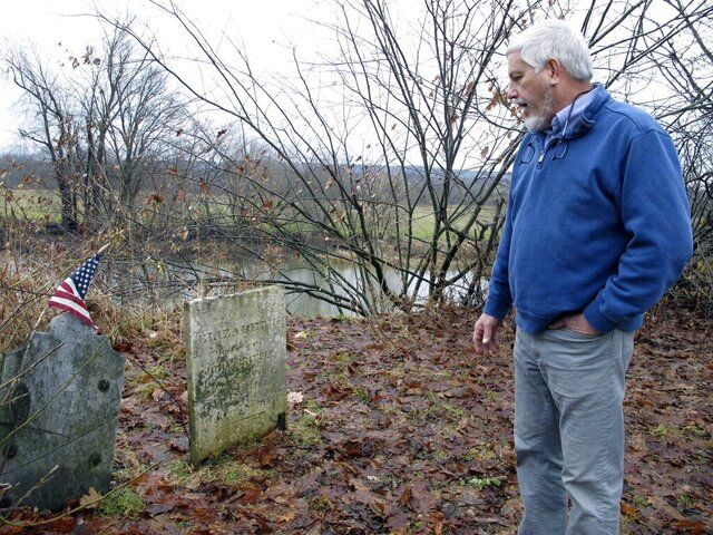 In this Dec. 10, 2019, photo, Don Mason, chairman of the Weybridge, Vt., selectboard looks at gravestone of Revolutionary War soldier William Haven, who is buried in a cemetery near the edge of an eroding river bank in Weybridge, Vt. Rising seas, erosion and flooding from worsening storms that some scientists believe are caused by climate change are putting some older graveyards across the country at risk. (AP Photo/Lisa Rathke)