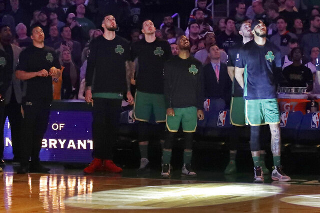 Boston Celtics players look top at a video tribute to the late Los Angeles Laker Kobe Bryant, before an NBA basketball game against the Golden State Warriors, Thursday, Jan. 30, 2020, in Boston. (AP Photo/Elise Amendola)