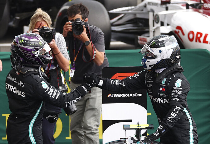 Race winner Mercedes driver Lewis Hamilton of Britain, left, celebrates with second placed Mercedes driver Valtteri Bottas of Finland after the Formula One Grand Prix at the Spa-Francorchamps racetrack in Spa, Belgium, Sunday, Aug. 30, 2020. (Lars Baron, Pool via AP)