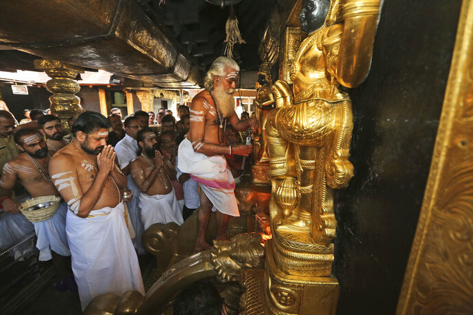FILE- In this Nov. 5, 2018, file photo, the head priest opens the sanctum sanctorum of the Sabarimala temple, one of the world's largest Hindu pilgrimage sites, in Kerala state, India. India's Supreme Court will set law on women's entry into temples and mosques after being asked to review its decision lifting a ban on some women entering the Sabarimala temple in Kerala state. (AP Photo/Manish Swarup, File)