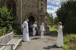 The Rev. Jonathan Gordon, left, and Assistant Vicar Miranda Sheldon, right, greet Anglican worshippers who attended their first communal prayer service after pandemic restrictions were eased, at St. Mary's Church, Northchurch in Berkhamsted, England, on Sunday, July 5, 2020. On March 24, the Church of England closed all its buildings.