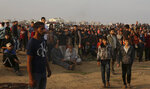 Protesters gather near the fence of Gaza Strip border with Israel during a protest east of Gaza City, Friday, Nov. 9, 2018. Gaza's Hamas rulers said Friday that deadly protests along Gaza-Israel perimeter fence have achieved some goals; $15 million from Qatar to help pay the salaries of civil servants. (AP Photo/Adel Hana)