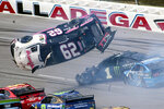 Brendan Gaughan (62) flips in Turn 3 during a NASCAR Cup Series auto race at Talladega Superspeedway, Monday, Oct 14, 2019, in Talladega, Ala. (AP Photo/Greg McWilliams)