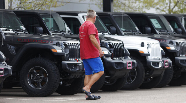 In this April 26, 2020, photo, a prospective buyer looks over a row of unsold 2020 Wranglers at a Jeep dealership in Englewood, Colo. To spur car sales amid the coronavirus pandemic, nearly every automaker has introduced 0% financing. Getting a 0% car loan can be a smart way to finance a new car. (AP Photo/David Zalubowski)