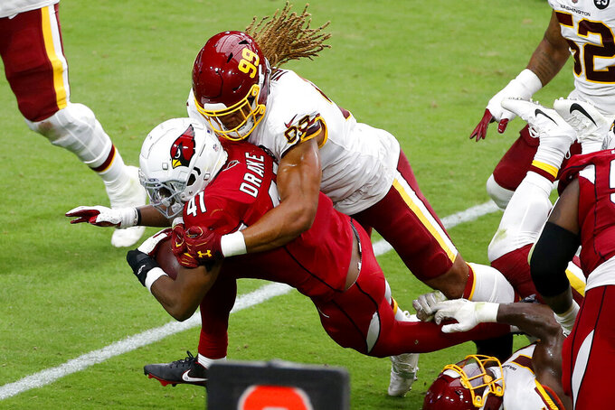Arizona Cardinals running back Kenyan Drake (41) is tackled by Washington Football Team defensive end Chase Young (99) during the first half of an NFL football game, Sunday, Sept. 20, 2020, in Glendale, Ariz. (AP Photo/Darryl Webb)