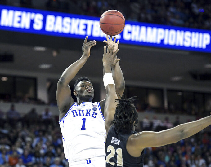 FILE - In this March 24, 2019, file photo, Duke forward Zion Williamson (1) attempts to shoot against Central Florida forward Chad Brown (21) during the first half of a second-round game in the NCAA men's college basketball tournament, in Columbia, S.C. Duke's Zion Williamson and R.J. Barrett are the second freshman teammates to earn first-team All-America honors.  Williamson and Barrett headed The Associated Press All-America team released on Tuesday, April 2, 2019, joined by Tennessee's Grant Williams, Murray State's Ja Morant and Cassius Winston of Michigan State. (AP Photo/Sean Rayford, File)