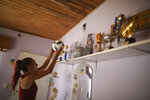 Soccer player Mara Gomez puts a ball back on the shelf full of her soccer trophies at her home in La Plata, Argentina, Thursday, Feb. 6, 2020. Gomez is a transgender woman who is limited to only training with her women's professional soccer team, Villa San Carlos, while she waits for permission to start playing from the Argentina Football Association (AFA). If approved, she would become the first trans woman to compete in a first division, professional Argentine AFA tournament. (AP Photo/Natacha Pisarenko)