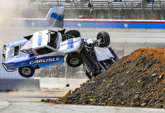 Matt Brabham, left, and Jeff Hoffman, right, collide on a jump attempt during the Outdoor Powersports Offroad Rumble SST Race prior to a NASCAR Cup auto race at Texas Motor Speedway, Sunday, March 31, 2019, in Fort Worth, Texas. (AP Photo/Larry Papke)