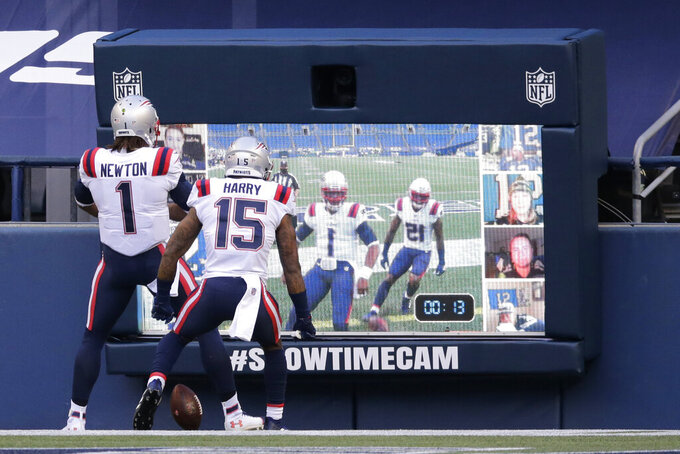 New England Patriots quarterback Cam Newton (1) and wide receiver N'Keal Harry (15) celebrate in front of a two-way video display after Newton scored a touchdown against the Seattle Seahawks during the first half of an NFL football game, Sunday, Sept. 20, 2020, in Seattle. (AP Photo/John Froschauer)