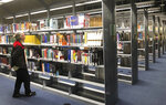 This Sept. 11, 2019 shows rows of books that soon will no longer be subject to overdue fines at Phoenix's Burton Barr Central Library. The public library system in November will join a growing number of libraries around the United States to drop overdue book fees. A unanimous City Council decision this week makes Phoenix, the fifth largest metropolis in the U.S., also the largest city to dump the fines. (AP Photo/Anita Snow)