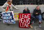 Pro-Brexit protestors show their posters in front of parliament in London, Wednesday, Oct. 23, 2019.  Britain's government is waiting for the EU's response to its request for an extension to the Brexit deadline. (AP Photo/Frank Augstein)