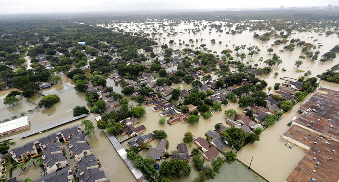 FILE - In this Aug. 29, 2017, file photo, a neighborhood near Addicks Reservoir is flooded by rain from Tropical Storm Harvey in Houston. A new study finds that FEMA buys flood-prone homes more often in wealthy, populous counties than in poor, rural areas, even though lower-income rural areas may be more likely to flood frequently. Harris County, Texas, where Houston is located, which, according to its flood control district, undergoes a major flood about every two years, has used FEMA's buyout programs more than any other county, the researchers said. (AP Photo/David J. Phillip, File)
