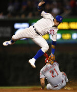 Chicago Cubs shortstop Javier Baez attempts to apply the tag as Cincinnati Reds' Michael Lorenzen (21) steals second base during the ninth inning of a baseball game Tuesday, July 16, 2019, in Chicago. (AP Photo/Paul Beaty)
