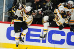 Boston Bruins center Brad Marchand (63) jumps into the arms of left wing Taylor Hall (71) after scoring the winning goal in overtime of Game 2 of an NHL hockey Stanley Cup first-round playoff series against the Washington Capitals, Monday, May 17, 2021, in Washington. (AP Photo/Alex Brandon)
