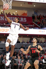 Connecticut guard Christian Vital (1) lays up a shot over Houston guard Quentin Grimes (24) during the first half of an NCAA college basketball game Thursday, Jan. 23, 2020, in Houston. (AP Photo/Michael Wyke)