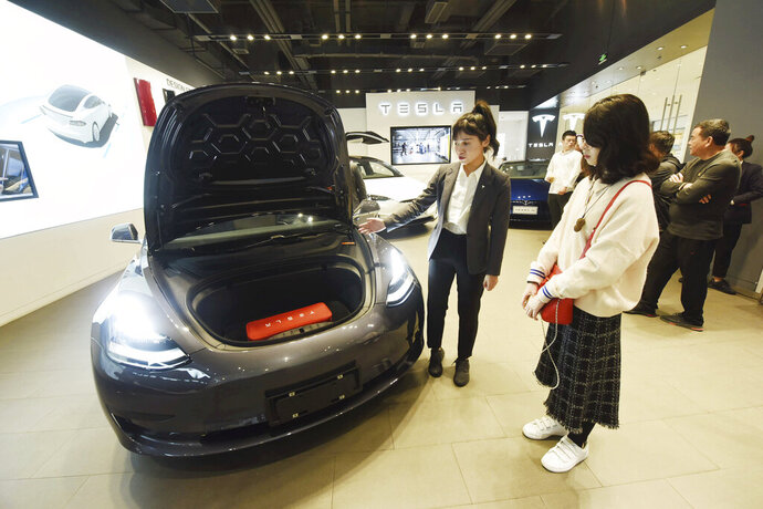 In this Nov. 24, 2019, photo, a saleswoman talks about a Tesla Model 3 car at a Tesla showroom in Hangzhou in eastern China's Zhejiang Province. Tesla's Shanghai factory delivered its first cars to customers Monday, Jan. 6, 2020, and chief executive Elon Musk said the electric automaker plans to set up a design center in China to create a model for worldwide sales. (Chinatopix via AP)